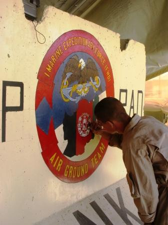 Cpl. John Coble works on a welcome sign for I MEF (Fwd.) in Afghanistan. (Photo by Dan Lamothe)