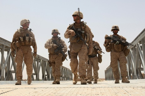 A security team led by Lt. j.g. Johnathan Flynn, center, officer in charge of Naval Mobile Construction Battalion 5, escorts Lt. Col. Brian Christmas, left, commander of 3rd Battalion, 6th Marines, across a newly-constructed bridge in northern Marjah, Afghanistan, on June 26. (Lance Cpl. Khoa Pelczar/Marine Corps)