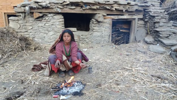 Image caption A menstruating woman crouches outside a mud hut in Krishnamaya's home village