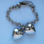 Fall in love two times over with Sterling silver charm bracelet featuring not 1 , but 2 large 3d hearts attached! 2 puffy sterling hearts (see Charms- Hearts/love) for full description attached to sterling thin linked chain. almost 8 inches long with 2 inch drop chain and clasp closure. Marked sterling.