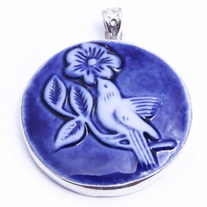 Nectar a beautiful round handcarved porcelain pendant, set in four colours.; blue, grey, light blue and red.