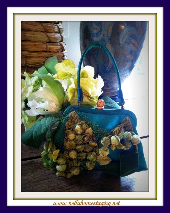 Green purse in front of lamp and flowers blue frame