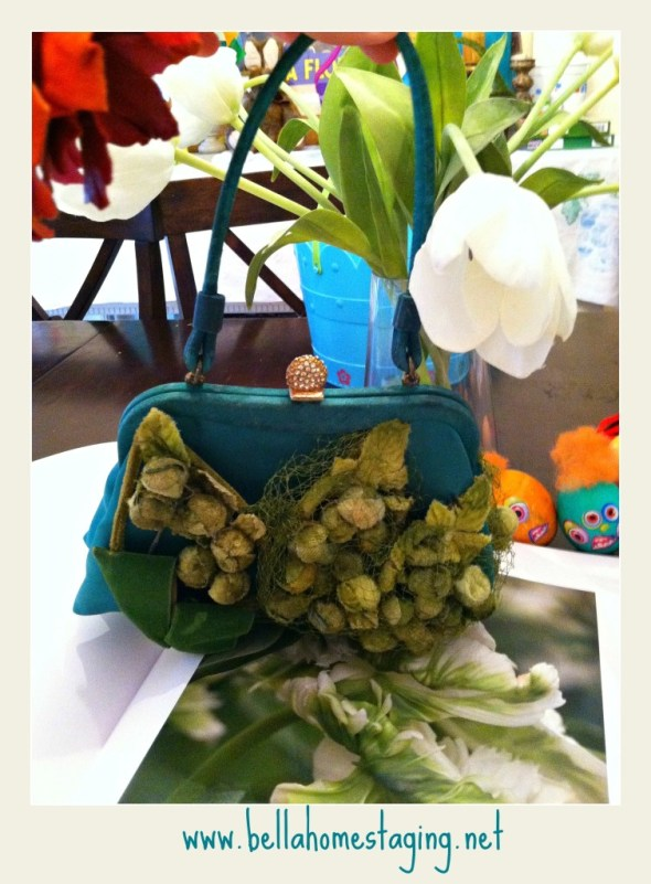 green purse in front of vase with easter eggs