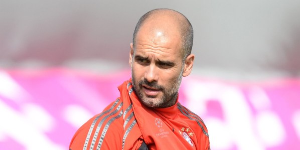 Bayern Munich's Spanish headcoach Pep Guardiola puts on his shirt during the final team training session on the eve of the second leg UEFA Champions League semi-final second leg match between FC Bayern Munich and FC Barcelona at the Bayern Munich trainings area in Munich, southern Germany, on May 11, 2015. AFP PHOTO / CHRISTOF STACHE