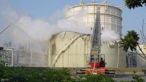 Kawasaki, JAPAN:  A fire engine fights a fire at an exploded oil tank, 10 meters (33 feet) both in height and diameter, at Toa Oil Co.'s refinery in Kawasaki city, Kanagawa prefecture, 21 May 2006.  The explosion occurred at an oil refinery in a city outside of Tokyo, but no casualties were immediately reported, Japanese police said. AFP PHOTO/JIJI PRESS  (Photo credit should read AFP/AFP/Getty Images)