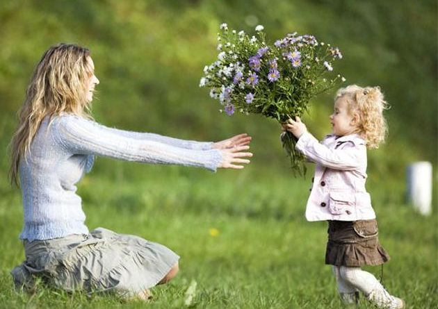 Daughter giving mother bunch of flowers, side view