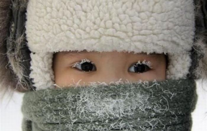 A child, with eyelashes covered with hoarfrost, is seen along a street in the eastern Siberian city of Yakutsk in Sakha (Yakutia) Republic February 10, 2012. The air temperature in Yakutsk is about minus 35 degrees Celsius (minus 31 degrees Fahrenheit).  REUTERS/Viktor Everstov  (RUSSIA - Tags: ENVIRONMENT SOCIETY TPX IMAGES OF THE DAY)