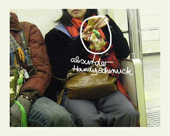 Frau in Tokioter U-Bahn hält übergroßen Kuscheltier-Handyanhänger