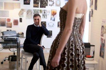 """Raf Simons checkt ein Vintage-Kleid von Dior (Szene aus """"Dior und ich"""" von Frédéric Tcheng)"""