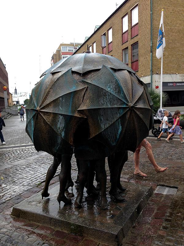 Skulptur mit Menschen unter Regenschirmen in Trelleborg