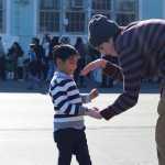 Senior Max Yera gives a handshake to a second grader.