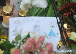A memorial card is seen at the mourning site dedicated to the victims of the twin attacks outside the Cathedral in Oslo, Norway, on July 24, 2011.  (Xinhua/Wang Qingqin)