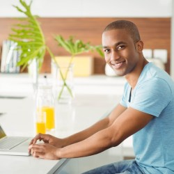 Smiling man using laptop