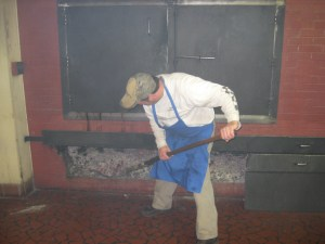 Tending the coals inside the smokehouse