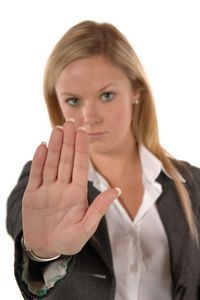 Blond women in business clothing with hand up signaling STOP