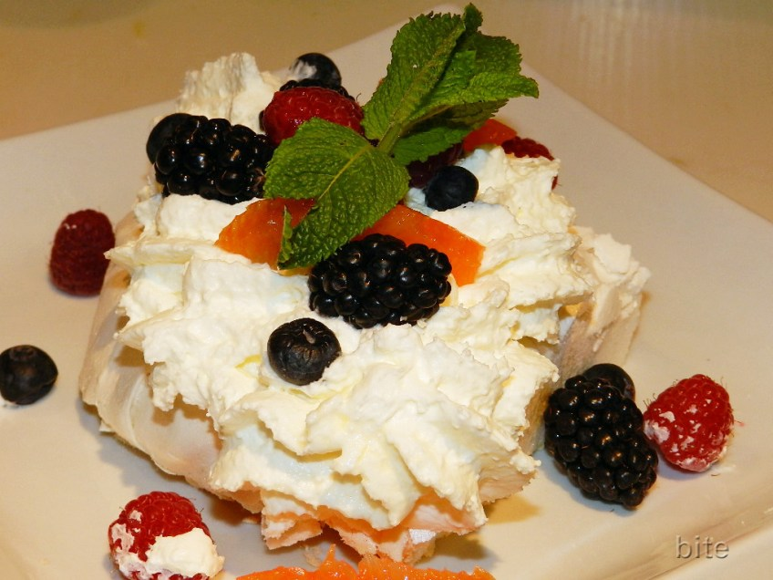 Pavlova with whipped cream, fresh fruit and a sprig of mint