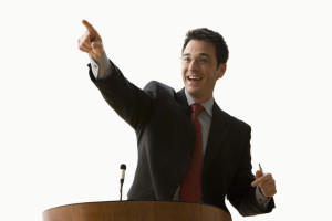 A young businessman is standing at a podium and pointing. Horizontal shot. Isolated on white.