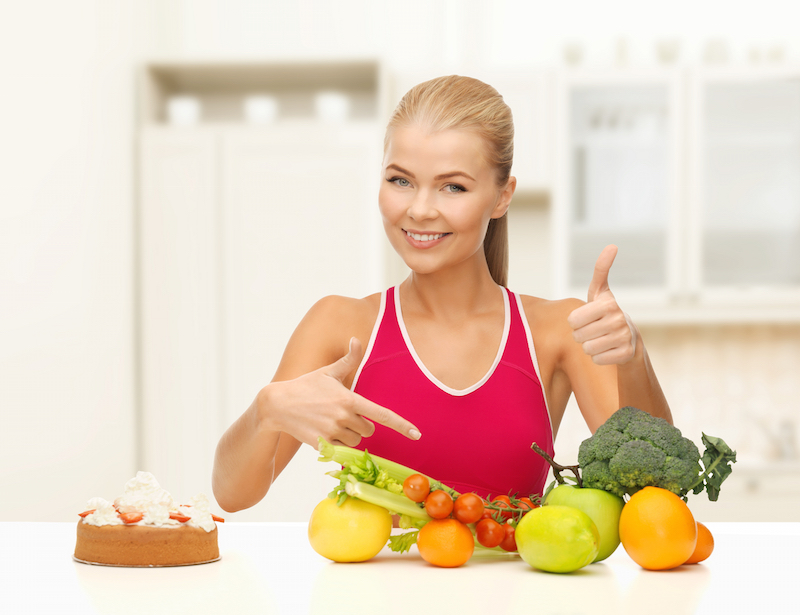 Bernardus Johannes Sleijster blog. fitness, healthcare and diet concept - smiling woman with fruits and cake pointing at healthy food detox