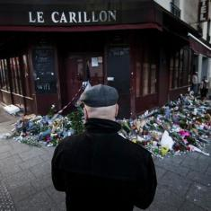 A man looks at the flowers and candles placed in front of the Carillon restaurant, in Paris, France, Nov. 15, 2015. (EPA/IAN LANGSDON)