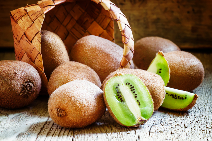 Kiwifruit poured out of a wicker basket, vintage wooden background, selective focus