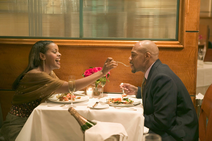 African American couple on date feeding each other