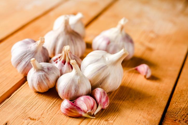 Raw garlic on wooden background