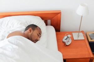 Young man sleeping next to Alarm Clock