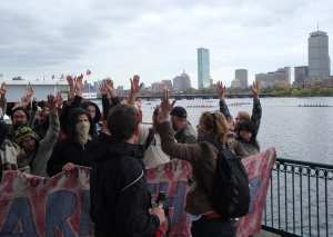 With the Boston skyline visible beyond crew teams on the Charles River, demonstrators use a hand signal to indicate approval during discussion. (Blast Staff photo/John Stephen Dwyer)