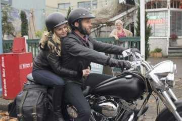 Emma (Jennifer Morrison) hops on the stranger's (Elon Bailey) bike, taking a leap of faith.