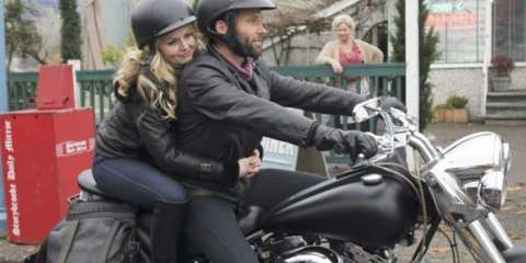 Emma (Jennifer Morrison) hops on the stranger's (Elon Bailey) bike, taking a leap of faith.