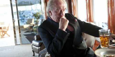 The nefarious and mysterious Michael (Michael Gambon) unnerves adversaries as he downs a morning scotch.