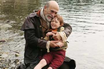 Geppetto (Tony Amendola) cradles his son, Pinocchio, after he's transformed from a puppet into a real boy.