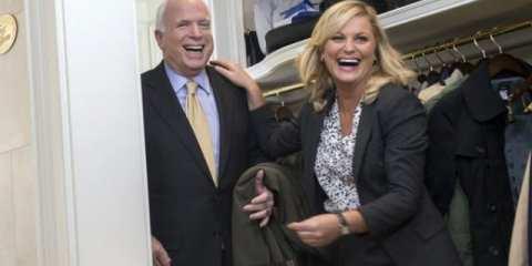 Leslie Knope (Amy Poehler) and John McCain goofing around in a coat room.