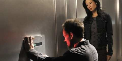 Sherlock (Jonny Lee Miller) tries to crack the code as Watson (Lucy Liu) stands by.