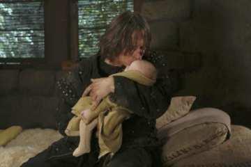 Rumpelstiltskin (Robert Carlyle) watches over his son.
