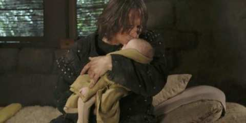 Rumpelstiltskin (Robert Carlyle) watches over his son.