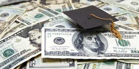 mini graduation cap on US money -- education costs