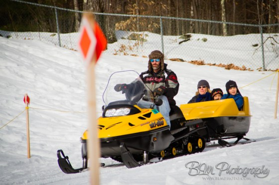 Chris Raymond giving Zach Pease & Friends a ride behind a snowmobile