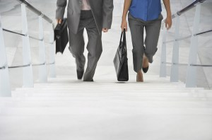 Lowsection of two businesspeople walking up stairs with bags in