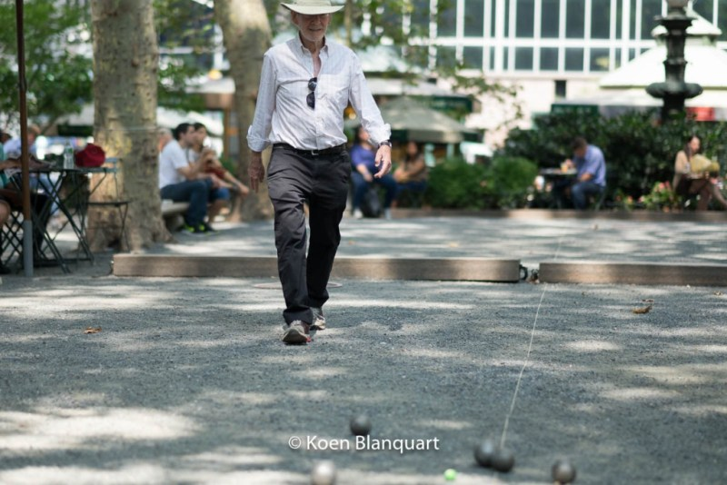 A man playing petanque in Bryant park