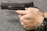 Minus your thumb and index finger, wrap the rest of your fingers around the grip of the pistol.
