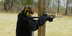 Woman shooting a red dot topped carbine rifle