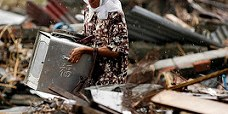 Seorang wanita Indonesia mengais sisa puing di bawah guyuran hujan, di bekas reruntuhan tempat tinggalnya. Foto milik U.S. Navy oleh fotografer Mate Airman Jordon R. Beesley/flickr.