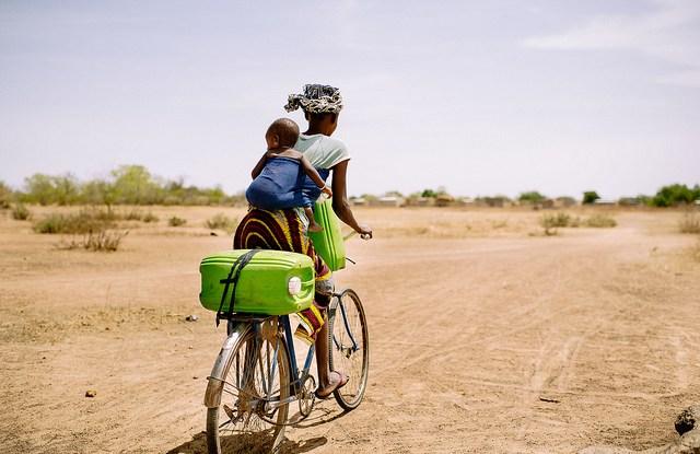 Barry Aliman, 24 tahun, mengendarai sepedanya bersama bayinya untuk mengambil air untuk keluarganya dekat Boromo, Burkina Faso. Sebuah peranti online berusaha melukiskan gambar yang jelas mengenai bagaimana hutan berkontribusi pada strategi adaptasi iklim penduduk pedesaan. Ollivier Girard/Foto CIFOR