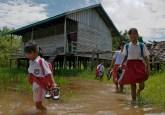 Murid SD di Danau Sentarum, Kalimantan Barat harus melepas sepatunya untuk meninggalkan kelas selama musim basah. Para periset bertujuan untuk mengetahui bagaimana hutan memengaruhi sensitivitas masyarakat terhadap peristiwa-peristiwa klimatis termasuk banjir, sekaligus juga mengetahui kapasitas adaptif mereka untuk meresponnya. Foto @CIFOR