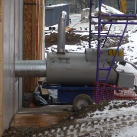 Propane heaters add warm air to the lower level of the construction area.