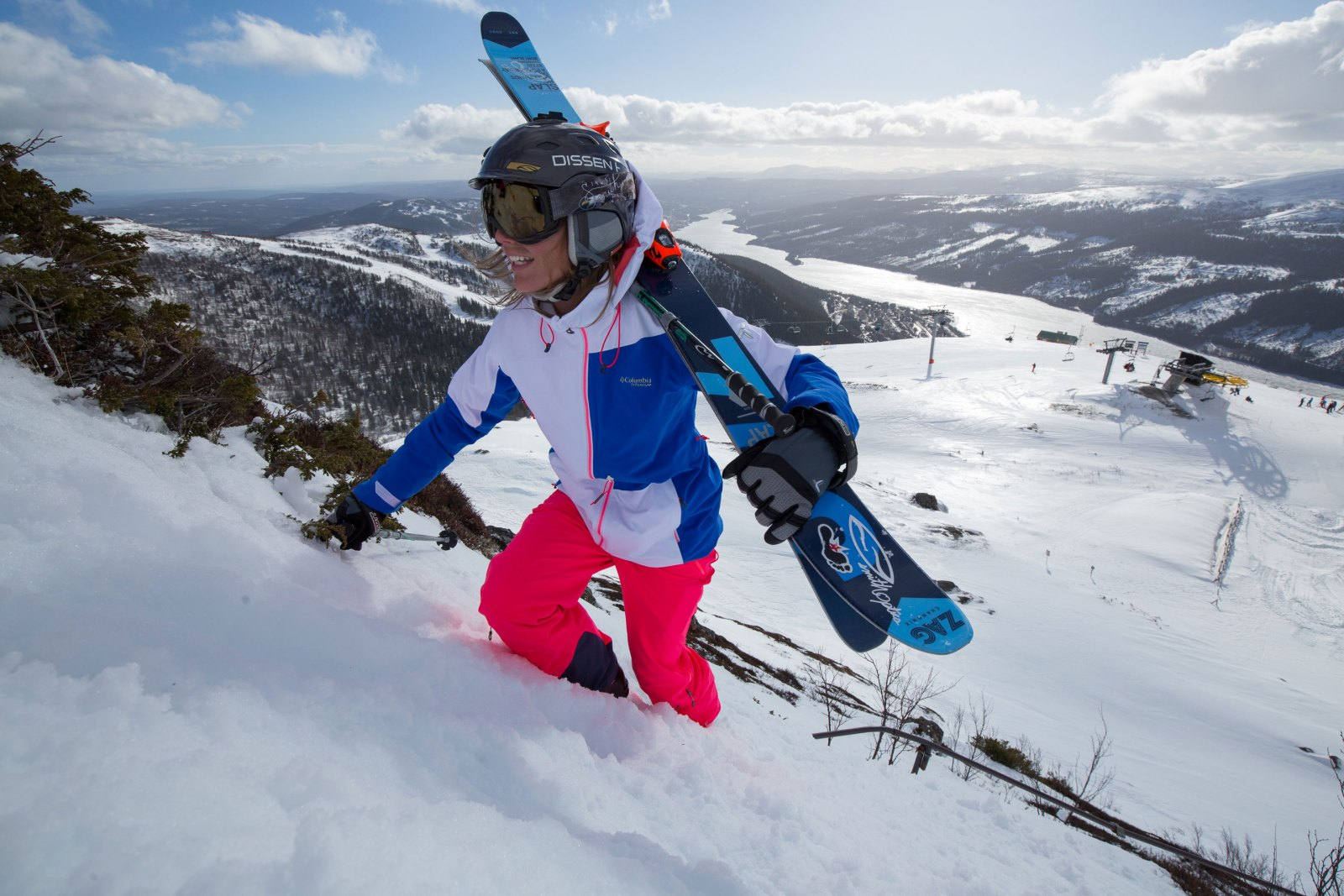 skier carrying her skis up a hill in Sweden