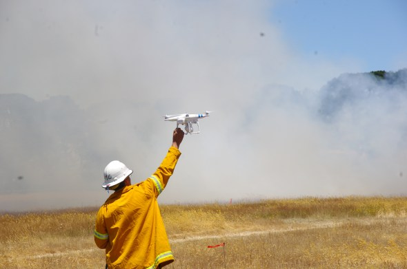 A scientist in fire gear holds up a UAV with smoke in the background