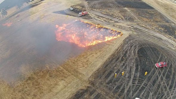 Aerial view of flames and smoke stretching across grasslands.