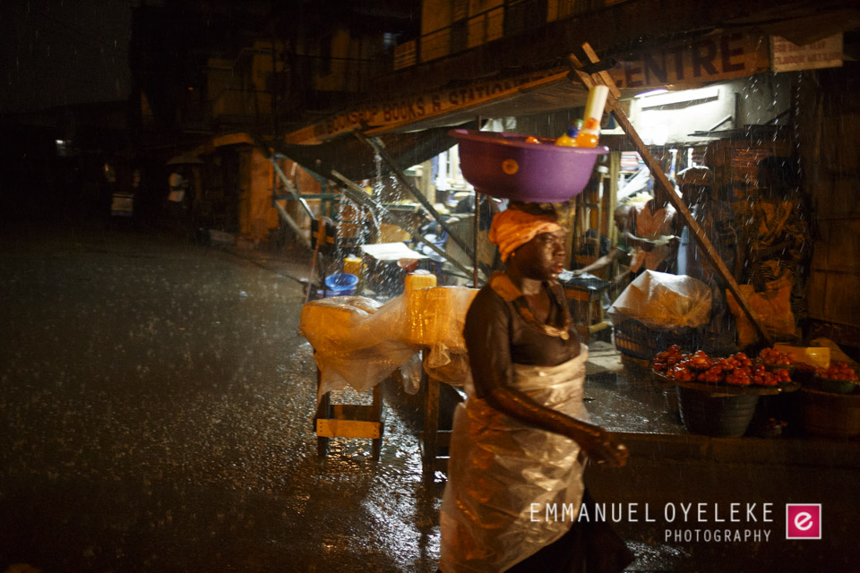 A woman wading through the rain with her goods on her head...I assume the nylon wrapper is to prevent the money she has made from getting wet...